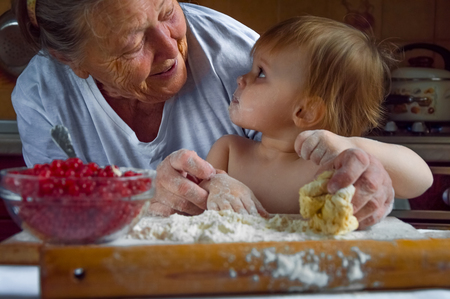 Portrait of faces, hands happy gray-haired granny, granddaughter. toddler girl play with baking, dough, flour on kitchen. child baby try cooking cookies, cake. Cozy family Look at each other