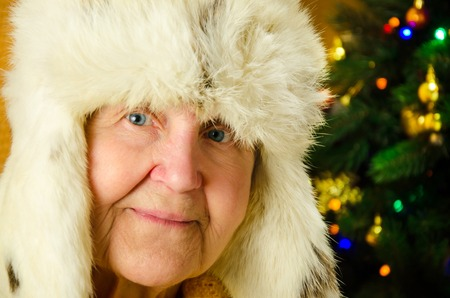Positive senior female is expressing happiness in holiday. Portrait of happy grandmother over decorated New Year tree, merry Christmas concept, happy family, lifestyle indoor,
