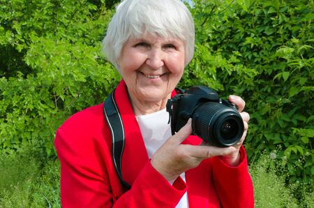 portrait of smile, happy grandmother enjoy her hobby at sun day. modern granny is professional photographer . photocamera in adult hand of old lady. pensioner use technology