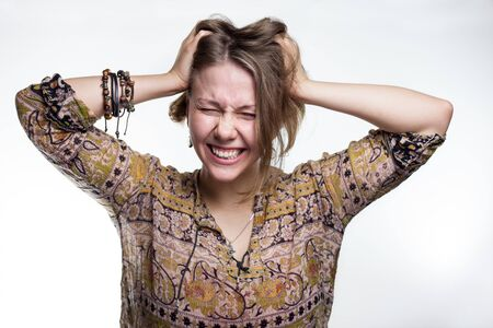 Emotions is stress, madness. concept crazy shouting. woman rending her hair. natural teenager screaming with close eyes and wide open mouth, holding hands on head. Sad blond girl