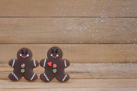 chocolate gingerbread cookies in the shape of men on a wooden board background. Foto de archivo - 138047742