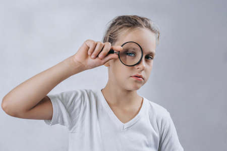 Little boy with magnifying glass on light background. Banque d'images