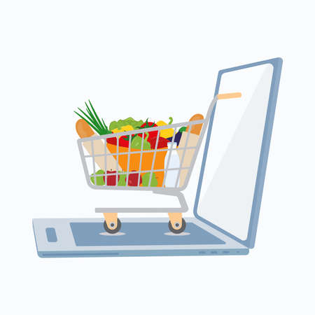Online shopping or e-commerce concept. Opened laptop and shopping cart with products.
