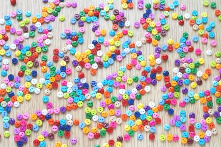 A lot of bright multicolored little buttons of red, yellow, blue, orange, pink, purple, green, white, color randomly lying on a wooden table. Top view.
