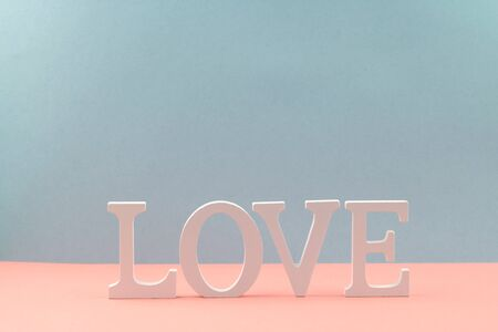 The word love of wooden white letters on a two-tone pink and blue background.
