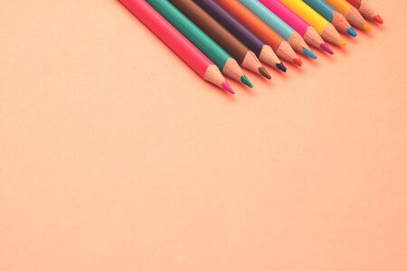 Colorful children colored pencils are in the color coral surface with blank space for label.