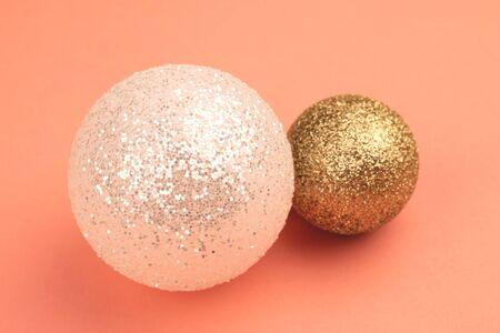 Two new years balls of white and gold color one more, the other less lie on a coral flat surface.