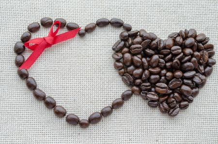 Two hearts of coffee beans on a textured bag photo