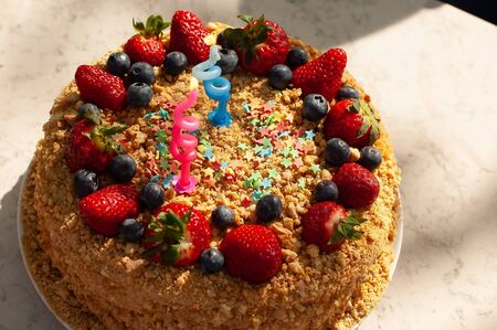 Party food concept. Homemade cake for Birthday decorated with candles, blueberries, strawberries Stock Photo