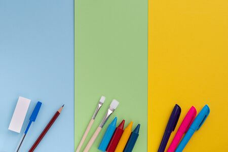 Back to school, minimalism concept. School supplies. Brushes for painting, pen, pencil, eraser, felt-tip pens on trendy blue green yellow color paper background. Copy space, flat lay