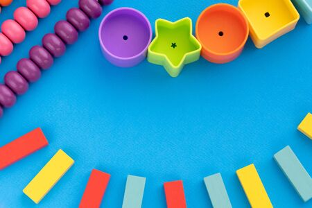 Frame from kids toys, top view on children's educational games on blue paper background. Multicolored wooden bricks, abacus, circles, stars. Flat lay, copy space for text. Stock fotó