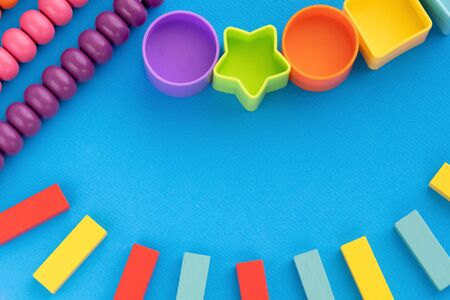Top view children educational games, frame kids toys blue paper background. Multicolored wooden bricks, abacus, circles, stars. Flat lay, copy space