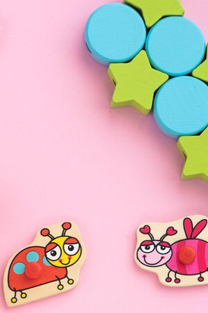 Top view on childrens educational toys, stars,circles on a pink background. Cute puzzle ladybug, bee. Flat lay, copy space for text. 版權商用圖片