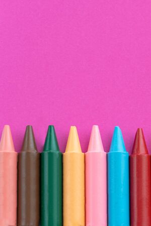 Back to school, minimalism concept. School supplies. Wax crayons on trendy purple color paper background. Copy space, flat lay.