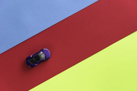 Kids toy car on trendy colorful background. Baby car top view on blue red yellow colored paper. Boys game. Travel and sport lifestyle. Business, transportation concept. Stockfoto