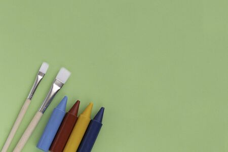 Back to school, minimalism concept. School supplies. Brushes for painting and wax crayons on pastel trendy green color paper background. Copy space, flat lay. 版權商用圖片