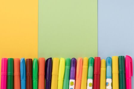 Back to school, minimalism concept. Felt-tip pens on pastel trendy blue green yellow color paper background. Copy space, flat lay