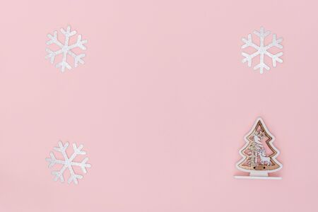 New Year and Christmas composition. Frame from snowflakes, chrismas tree on pastel pink paper background. Top view, flat lay, copy space.