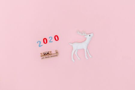 New year 2020, Christmas frame, greeting card. White deer with Santa's sleigh on pastel pink paper background. Top view, flat lay