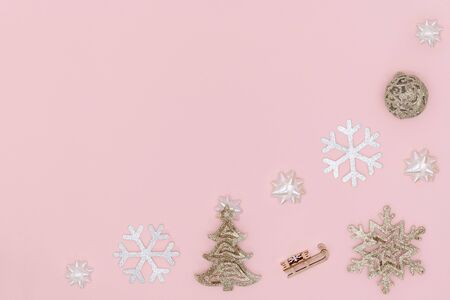 New Year and Christmas composition. Frame from golden christmas ball, snowflake, chrismas tree, gift bows, sleigh on pastel pink paper background. Top view, flat lay, copy space
