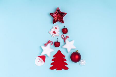 New Year and Christmas composition in the form of chrismas tree. Red and white decorations - stars, christmas balls, toys on pastel blue paper background. Top view, flat lay, copy space