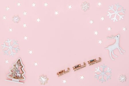 New year, Christmas frame, greeting card. White stars, snowflakes, chrismas tree, deer on pastel pink paper background. Top view, flat lay, copy space.
