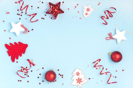 New Year and Christmas composition. Frame from red balls, white stars, chrismas tree and sparkles on pastel blue paper background. Top view, flat lay, copy space Foto de archivo