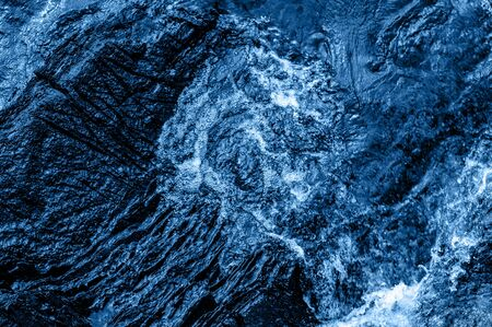 Texture of blue swirly sea water flowing surface background. Trendy color of the year 2020.