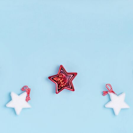 New Year and Christmas composition. Red and white christmas stars on pastel blue background. Top view, flat lay, copy space Stock Photo