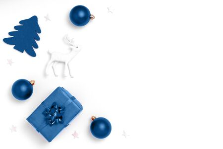New Year and Christmas composition. Frame from red balls, white stars, chrismas tree, deer on white paper background. Top view, flat lay, copy space. Trendy color of the year 2020.