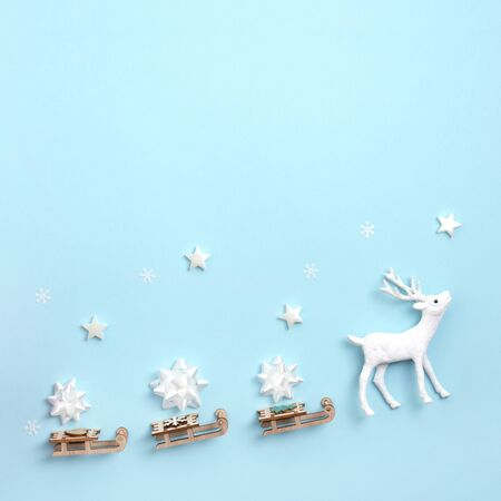 New year, Christmas frame, greeting card. Deer with Santa's sleigh on pastel blue paper background. Top view, flat lay, copy space.