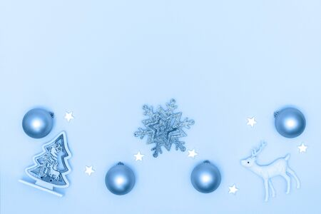 New Year and Christmas composition. Frame from balls, white stars, snowflake, chrismas tree, deer on pastel blue paper background. Top view, flat lay, copy space. Trendy color of the year 2020. Stock Photo