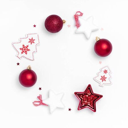 New Year and Christmas composition. Wreath from red balls, white stars, chrismas tree, deer on white paper background. Top view, flat lay, copy space