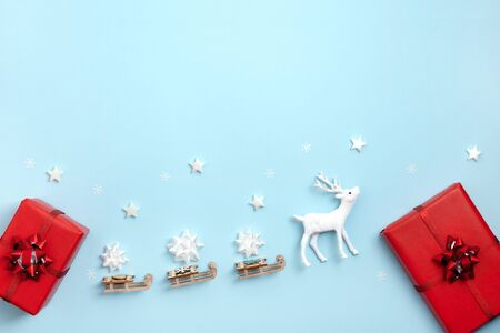 New year, Christmas frame, greeting card. White stars, deer with Santa's sleigh, gift boxes on pastel blue paper background. Top view, flat lay, copy space.
