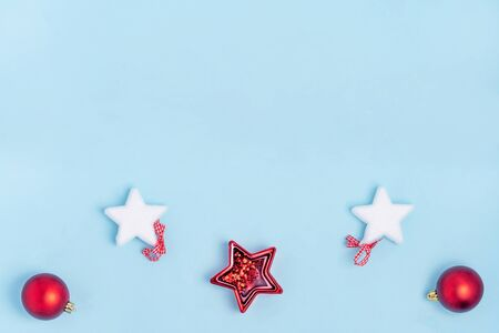 New Year and Christmas composition. Red and white christmas toys - stars, christmas balls on pastel blue background. Top view, flat lay, copy space