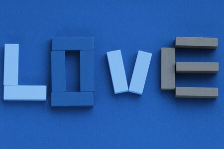 Word LOVE made from wooden bricks on blue background. Top view, flat lay. Trendy color 2020