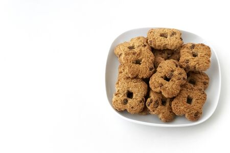 Chocolate chip cookies in ceramic white plate on white background. Top view, copy space, from above, flat lay