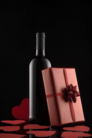 Gift box, wine bottle and red hearts on black background. Romantic greeting card and invitation. Valentines day composition.