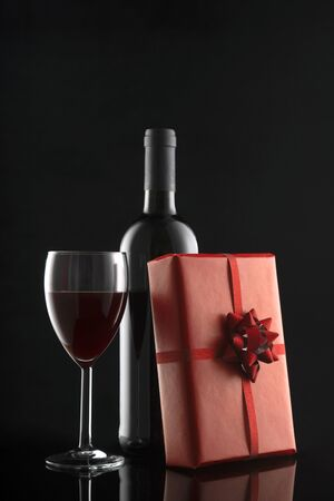 Gift box, wine bottle and wineglass on black background. Romantic greeting card and invitation. Valentine's day composition. Wedding day, Christmas, New year. Holiday concept