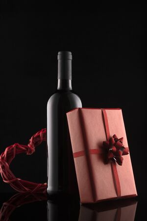 Gift box, wine bottle and red hearts on black background. Romantic greeting card and invitation. Valentine's day composition.