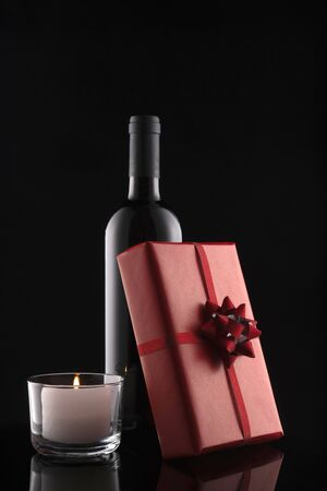 Gift box, bottle of wine, candle on black background. Valentine's day. Wedding day. Romantic greeting card and invitation.