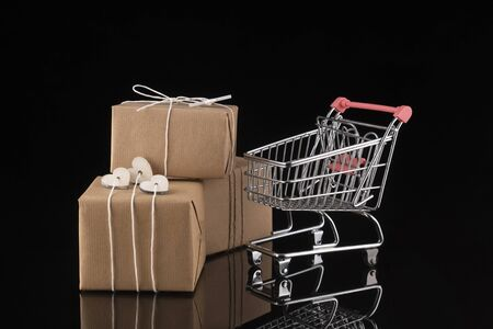 Shopping trolley cart and gift boxes on black background. Buying presents concept, online shopping. Isolated Stock Photo