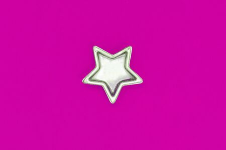 Christmas five pointed golden star on pink background. Christmas shining decoration. Holiday concept