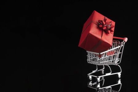 Shopping trolley cart and gift box on black background. Buying presents concept, online shopping. Isolated, banner, copy space