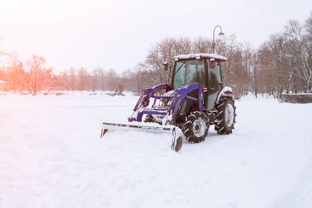 Tractor cleaning snow in a park Archivio Fotografico