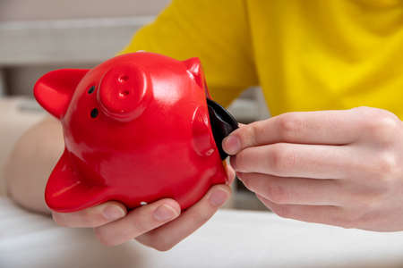 Female hands open a piggy bank to check the contents on the table at home.