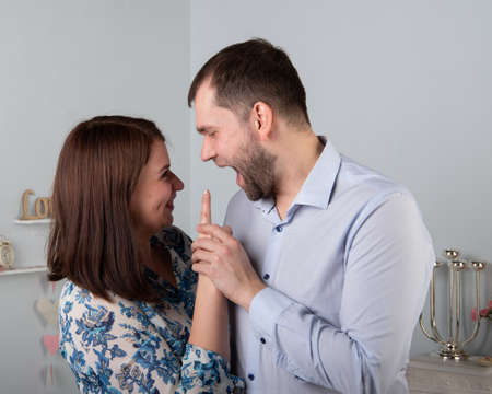 Angry husband yells at his wife. A woman threatens with a forefinger to a man. Unhappy married couple, relationship concept.