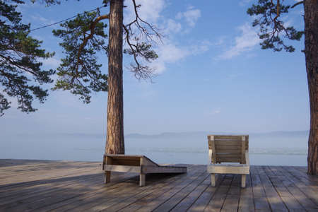 Spring morning, by the lake on which the snow melts, there are two empty deck chairs, pine trees grow nearby, there are no people around. The concept of loneliness, relaxation