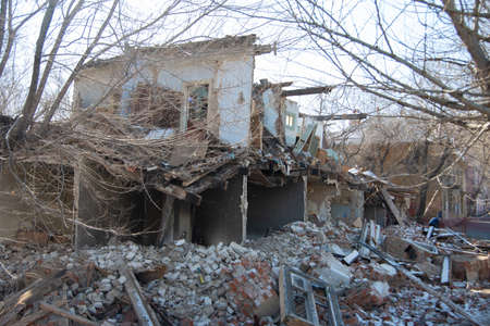 dismantling of an old building, collapsed from a cataclysm or old age, a building without a wall and a roof with a rickety second floor, a bunch of bricks and rubbish