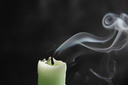 extinct light green candle with spectacular abstract smoke of a fanciful shape on a black background, close-up, abstraction.